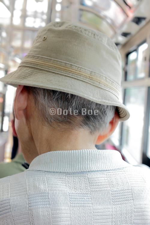back of elderly man wearing a hat