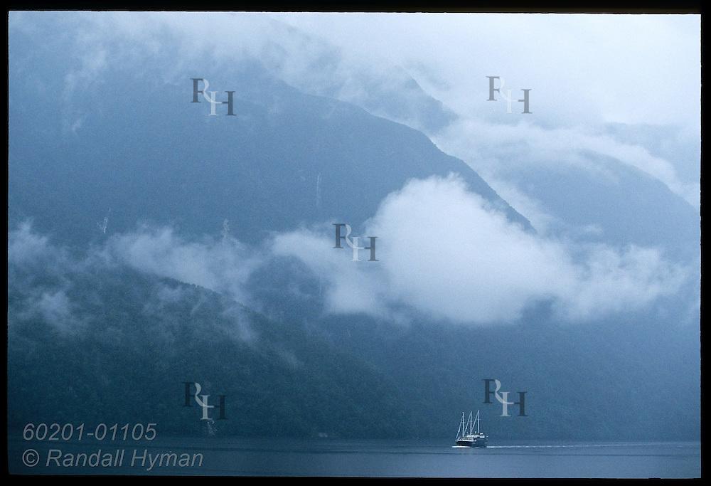 Three-masted sailing ship cruises past cloud-shrouded mountains of Doubtful Sound; Fiordland National Park, New Zealand.