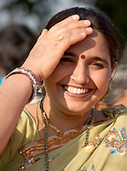 A smiling woman wearing jewelry including a necklace, earings, a ring, a nose ring and bangles; New Delhi, India