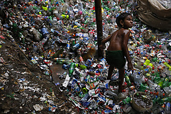August 3, 2017 - Dhaka, Bangladesh - JULEKHA (7), a child laborer works in the rain on a plastic bottle recycle factory near Kamrangirchar. After finishing school, she came here to help her mother. (Credit Image: © Md. Mehedi Hasan via ZUMA Wire)