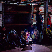 Young visitors sitting on the floor in one of the former prisoner barracks at the Auschwitz-Birkenau Nazi concentration camp close to Krakow in Poland. A woman is reading an eyewitness account of a former prisoner with the help of a torch. After a while she can not continue reading and starts to cry, she is passing the paper to somebody else who reads further. It is estimated that between 1.1 and 1.5 million Jews, Poles, Roma and others were killed in Auschwitz during the Holocaust between 1940-1945. The 27th of January 2015 is the 70th anniversary of the liberation of Auschwitz. #humanrights #documentary #photojournalism #panospictures #panos #auschwitz #poland #krakow #concentrationcamp #genocide #thirdreich #history #konzentrationslager #documentary#easterneurope #politics #prison #museum#people #prison #memorial #70th #anniversary