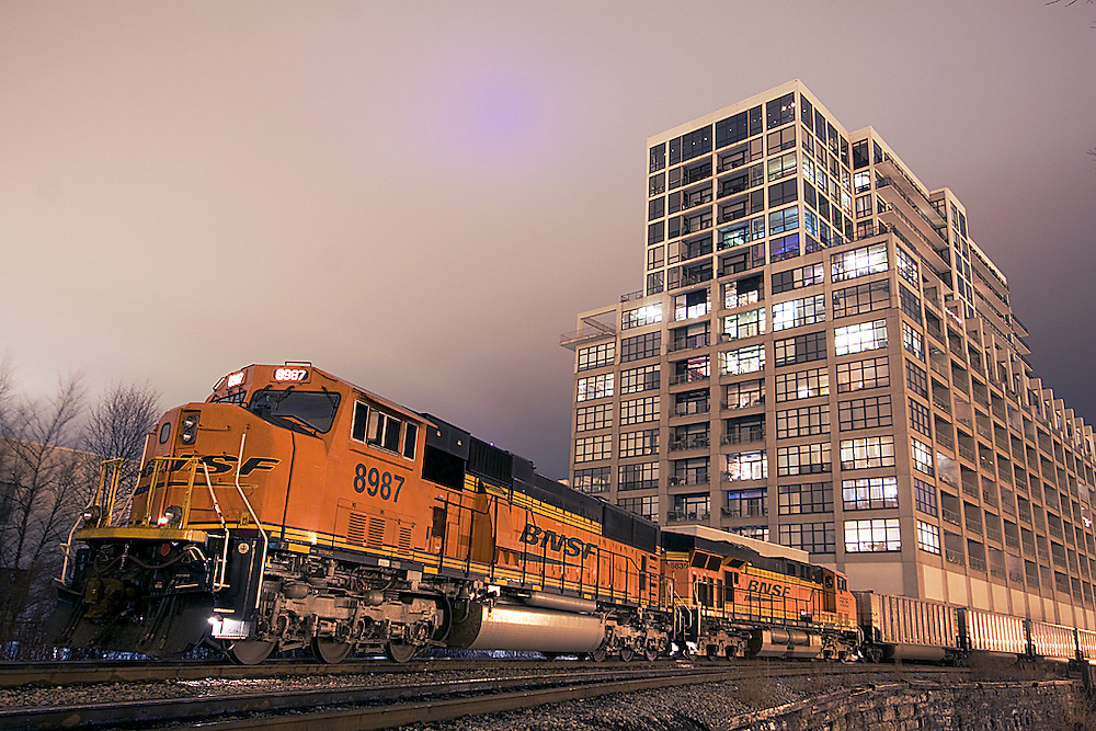 A run-thru BNSF empty coal train sits on the Canadian National's mainline through Chicago waiting for a new crew to take it west. In the background stands a new modern condo building made from a converted warehouse here in Chicago's up and coming South Loop neighborhood.