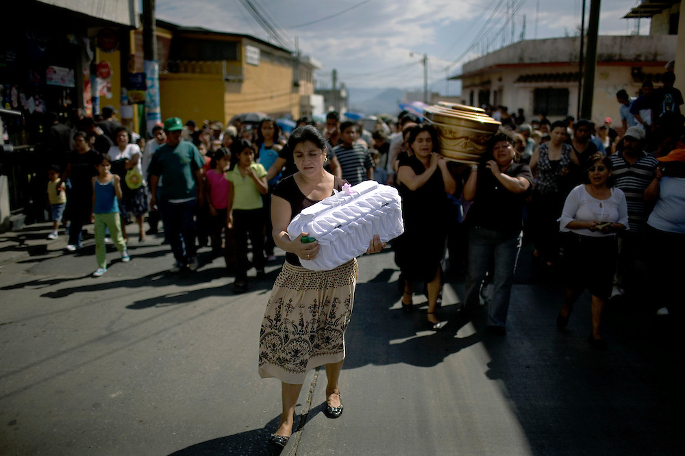 Neighbors carry the coffins of Ingrid Marisol Canis, 16, and her 8 months daughter after the pregnant mother was murdered by unknown assailants, Guatemala City, Friday, Feb. 20, 2009. Guatemala's constant streak of murders ,17-a-day,  provide a steady flow of customers to unregulated  funeral homes, where funeral workers can embalm corpses in the back of auto repair shop or rush to crime scenes to gather information that will allow them to locate, notify and make a sales pitch to the bereaved relatives.