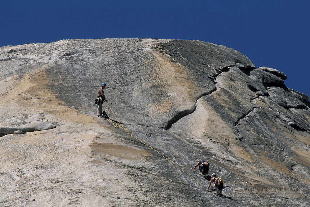 Mountain rock climber climbing on granite wall of Polly Dome, Yosemite National Park, California