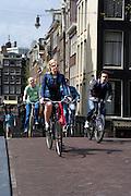 Fietsers rijden over een brug op de Keizersgracht in Amsterdam