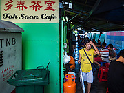 17 NOVEMBER 2016 - GEORGE TOWN, PENANG, MALAYSIA:  A local woman leaves Toh Soon Cafe in George Town, Penang, Malaysia. Toh Soon Cafe is one of the most popular places in George Town for a typical Malaysian breakfast on half boiled (soft boiled) eggs and toast served with Penang white coffee. It's located in a small alley off Campbell Street and on most mornings there's a long line to get a seat. George Town is a UNESCO World Heritage city and wrestles with maintaining its traditional lifestyle and mass tourism.       PHOTO BY JACK KURTZ