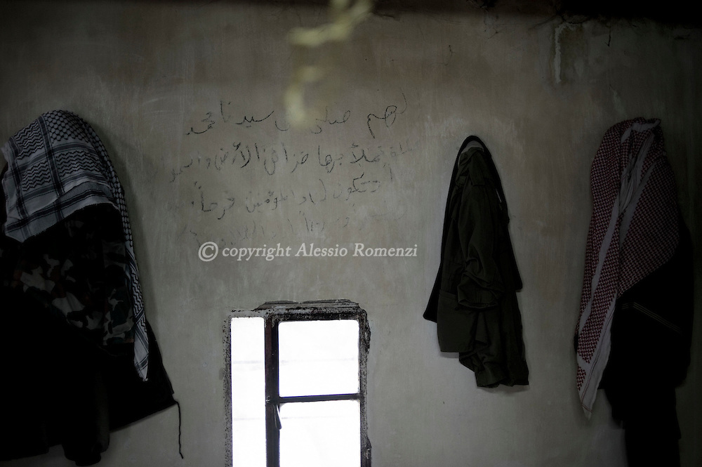 """SYRIA - Homs province: This picture shows the interior of a house used as a weapon deposit by the Free Syrian Army. The writing on the wall says  """"Mohammad is the prophet and the muslims, the sky and the earth are proud of him""""  on February 18, 2012. ALESSIO ROMENZI"""