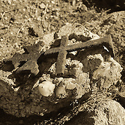 An ornate cross laying on a stone marks a grave site at the pioneer cemetery in Old Congress, AZ