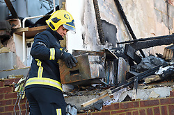 © Licensed to London News Pictures. 22/10/2018. LONDON, UK.  A firefighter examines a burnt filing cabinet at the site of a fire in a first-floor flat, caused by a suspected gas explosion, in Fulbeck Way, Harrow, north west London, which took place in the early hours of 21 October.  It has been reported that a woman died at the scene, and another woman, a man and a baby were rescued from the property. Investigations continue as to the cause of the fire. Photo credit: Stephen Chung/LNP