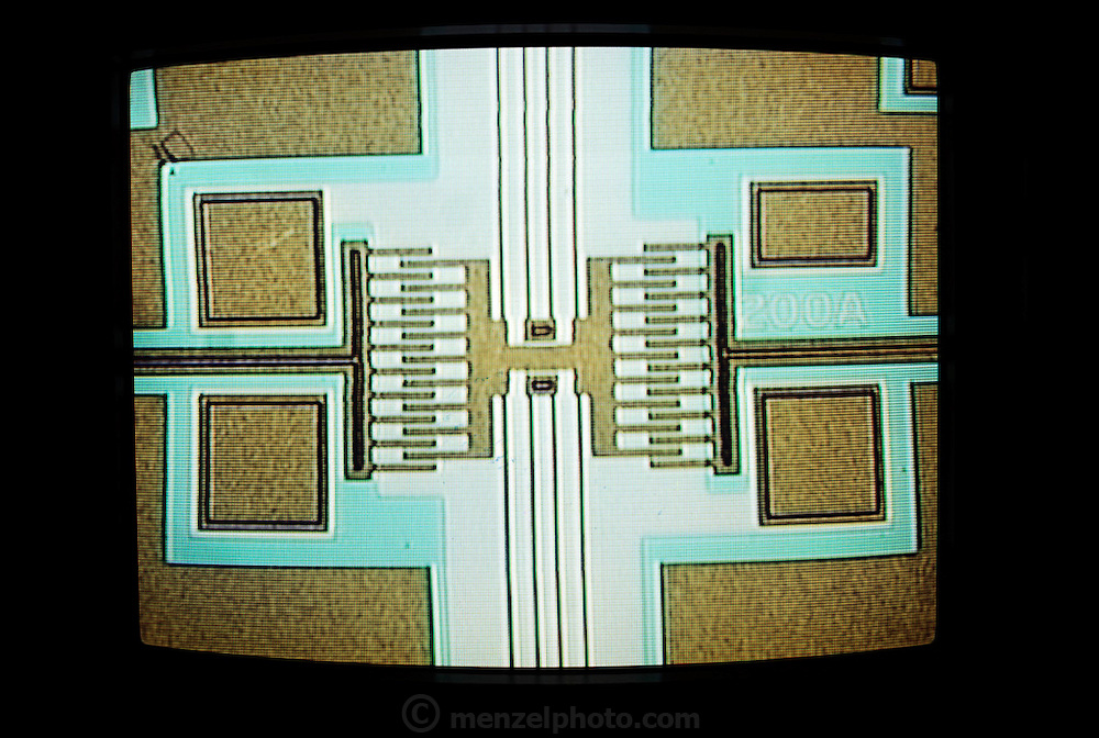 Micro Technology: Micromechanics: Light micrograph of the detector 'teeth' of a micro-resonator. This is a tiny mechanical resonating structure, made by the same silicon deposition process used in the manufacture of microcircuits. The 'teeth' seen here detect the motion of the resonator, the central buff-colored object. The dark vertical lines running above and below the resonator are the strands of silicon connecting the sensor to the resonant masses. The strands are only two microns thick, but at this scale silicon has a greater mechanical strength than steel. Micro-resonators have a variety of uses in detecting very small amplitude motions. [1989]