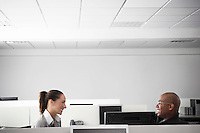 Two office workers sitting face to face in office cubicle smiling profile