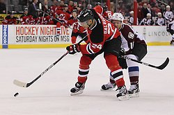 Mar 15; Newark, NJ, USA; New Jersey Devils defenseman Bryce Salvador (24) plays the puck while being defended by Colorado Avalanche center Jay McClement (16) during the first period at the Prudential Center.