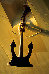 Anchor hanging from a large tanker at sunset