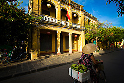 A vietnamese woman rides on bicycle loaded of bananas. A french colonial style house is hit by early sun. Hoi An, Vietnam, Asia 2012.