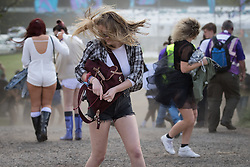 © Licensed to London News Pictures .06/06/2015. Manchester , UK.  Festival goers walk backwards in to strong gusts of wind stirring up dust and grit . Early arrivals at The Parklife 2015 music festival in Heaton Park , Manchester . Photo credit : Joel Goodman/LNP