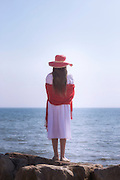 a girl in a white dress with red sunhat and shawl is standing on rocks at the sea