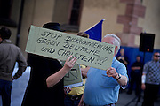 Frankfurt am Main | 18 May 2015<br /> <br /> On monday (May 18, 2015) less than 25 followers of PEGIDA movement gathered for a rally against Islam, muslims and refugees at Hauptwache square in front of Katharinenkirche in the german city of Frankfurt am Main. The PEGIDA rally was countered by protests of about 800 left-wing antifascist activists. The picture shows PEGIDA followers with a cardboard wich reads &quot;Stop Diskriminierung gegen Deutsche und Christen!&quot; (Stop discrimination of germans and christians).<br /> <br /> &copy;peter-juelich.com<br /> <br /> [No Model Release | No Property Release]