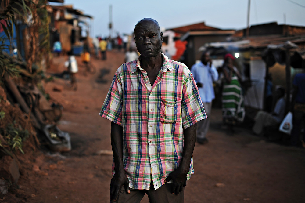 12-03-22   -- KAMPALA, UGANDA --  Charles Okongo, from Kitgum, stands in the street in a drunken stupor. Alcoholism is prevalent in the Acholi Quarter, as many try to forget their traumatic past. Since the early 1990's, people from the Acholi tribe (and from other northern tribes) migrated to a plot of land in a suburb of Kampala to escape the violence in the north. Now, rather than returning to their ancestral lands, some are calling the Acholi Quarter home. Many residents, unable to find well-paying employment, make a living mining and crushing rocks by hand.. Photo by Daniel Hayduk
