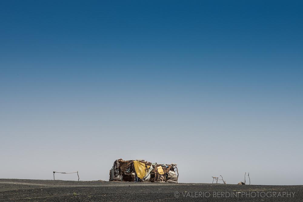 "A hut built in what berbers call ""black desert"", the dark vulcanic stones rich area surrounding the sand dunes in Merzouga."