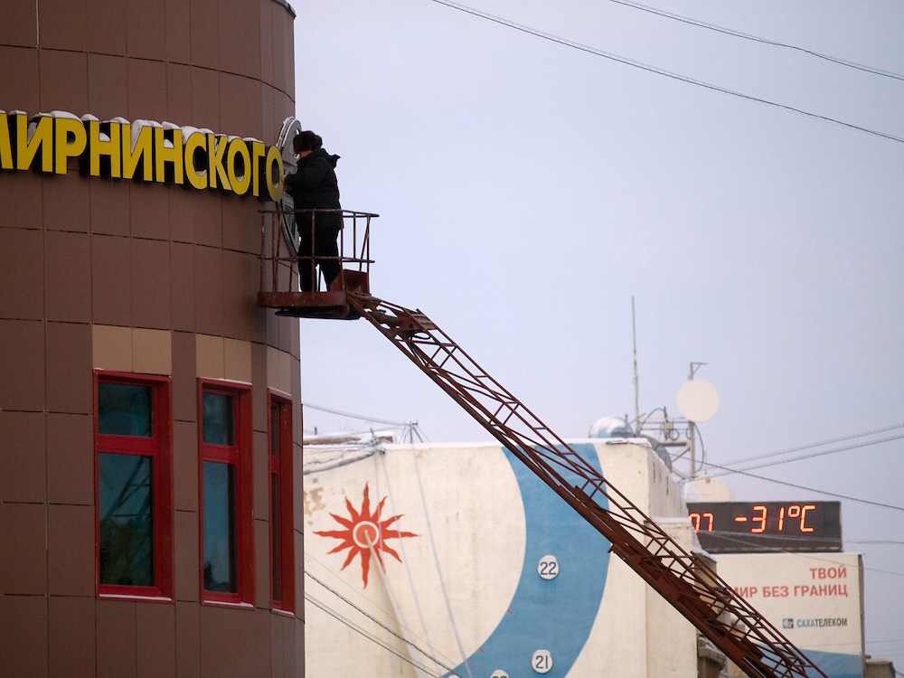 Worker cleaning a sign of the Polar Hotel in Yakutsk from snow. Yakutsk is a city in the Russian Far East, located about 4 degrees (450 km) below the Arctic Circle. It is the capital of the Sakha (Yakutia) Republic (formerly the Yakut Autonomous Soviet Socialist Republic), Russia and a major port on the Lena River. Yakutsk is one of the coldest cities on earth, with winter temperatures averaging -40.9 degrees Celsius.