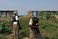 Deminers from Mines Advisory Group (MAG) clear an area around a former military barracks and weapons store used by northern government forces during Sudan's civil war. The building is next to an open area near the John Garang memorial where Independence ceremonies will be held on July 9th, 2011. The area is heavily contaminated with unexploded ordinance (UXO). The Government of South Sudan asked MAG to help SPLA deminers clear the area before the independance celebrations..Juba, South Sudan. 05/07/2011..Photo © J.B. Russell