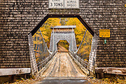 The Wire Bridge is a historic span in New Portland, Maine that crosses the Carrabassett River. It was built in the 1860's is the only surviving bridge of its type in the US. The unique cedar shingles on the side create a beautiful frame for this fall scene.