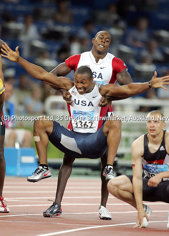 Men's 200m winner Shaun Crawford picks up his team mate after the race. Olympic Stadium, Athens, Greece.<br />