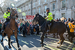 London, UK. 15th February, 2019. Mounted police officers struggle to control their horses as thousands of students stage an impromptu march in Whitehall during YouthStrike4Climate for Climate Day. After gathering in Parliament Square, students blocked streets around Westminster for around an hour. Strike events involving schools all over the UK were organised by UK Student Climate Network and the UK Youth Climate Coalition to demand that the Government declare a climate emergency and take positive steps to address the climate crisis, including highlighting the issue as part of the school curriculum, as well as lowering the voting age to 16.