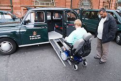 Woman wheelchair user accessing taxi via ramps,