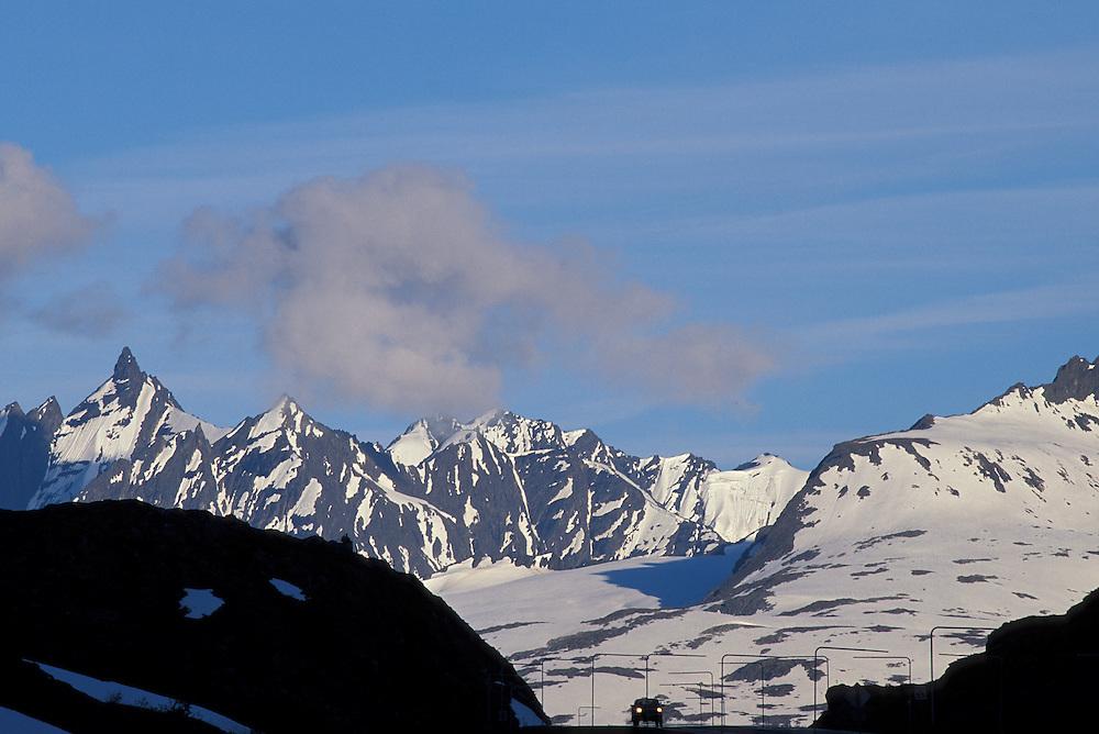 USA, Alaska, Chugach National Forest, Lone car crests Thompson Pass along Richardson Highway north of Valdez  .