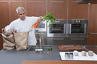 Mid- adult chef lifting carrots into sink