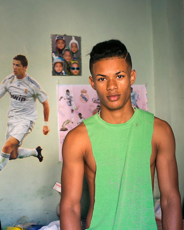 Teenager soccer fan who has put in his room a poster of Ronaldo , star of the Spanish Team REal Madrid.