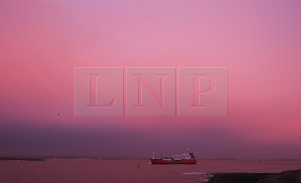 © Licensed to London News Pictures. <br /> 09/12/2014. <br /> <br /> Teesside, United Kingdom<br /> <br /> A container ship makes her way into Teesport as a beautiful sunrise casts a hue over clouds at the start of the day over Teesside. Strong winds are expected to pick up through the day as the winter weather continues.<br /> <br /> <br /> Photo credit : Ian Forsyth/LNP