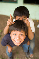 Boys mug for the camera after showing us the destruction of their school from a mudslide, Panabaj, Guatemala.