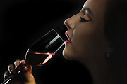 Sensual low key portrait of pretty young woman bringing wine glass to her lips.