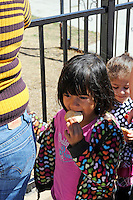 Children eat cookies while they wait in line for food distributed once a week at St. Clare's Corner, established in Salinas by the Franciscan Workers of Junipero Serra in 1982. Supplied by the Food Bank of Monterey County, basic foodstuffs like rice and beans supplement family diets from October to May, the winter months when unemployment is highest.