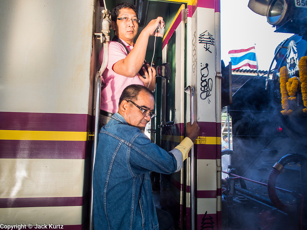 "05 DECEMBER 2013 - BANGKOK, THAILAND:  People stand in the the doorway of a special steam engine train leaving Hua Lamphong Train Station on the 86th birthday of Bhumibol Adulyadej, the King of Thailand. Dec. 5, the King's Birthday, is a national holiday in Thailand, and is also celebrated as the country's ""Fathers' Day."" The State Railways of Thailand put on special trains to take people to the King's ""Summer Palace"" in the oceanside community of Hua Hin where the King granted a public audience. There were also merit making ceremonies throughout the country.  Many people wear yellow on the King's Birthday because yellow is the color associated with his reign. As of 2013, he was the longest reigning monarch in the world.          PHOTO BY JACK KURTZ"