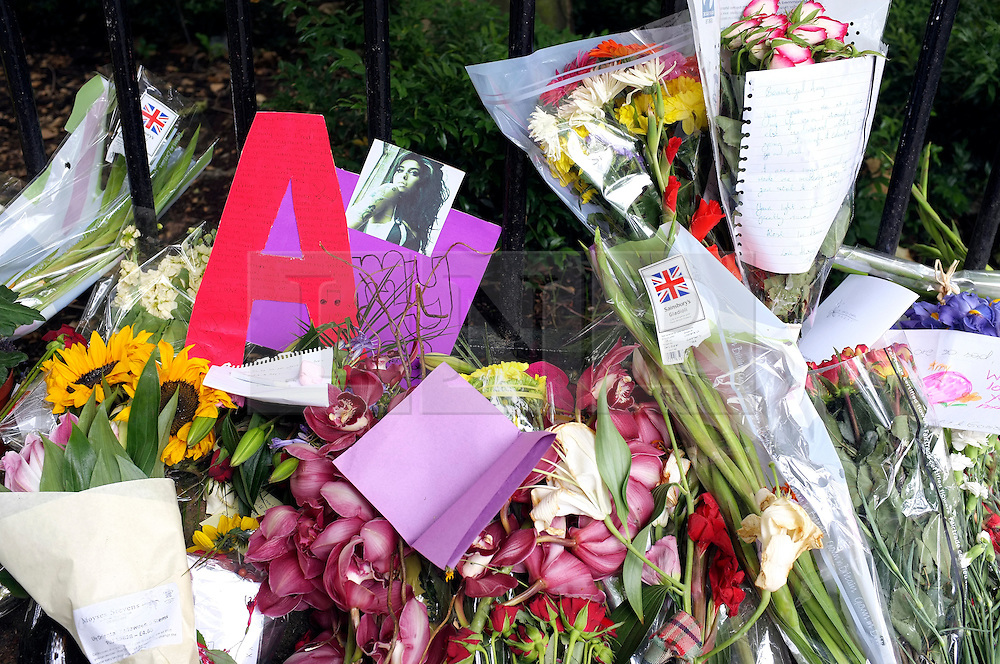 © licensed to London News Pictures. LONDON, UK.  26/07/11. On the day of her funeral fans look at flowers outside the Camden house of Amy Winehouse in North London today (26 July 2011). The singer passed away on Saturday 23th July. Mandatory Credit Stephen Simpson/LNP