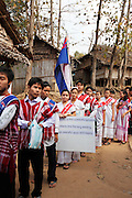 Karen refugee teenagers carry the Karen flag and boards asking for peace and an end to the Burmese war during the Revolutionary Day service in Mae La camp.