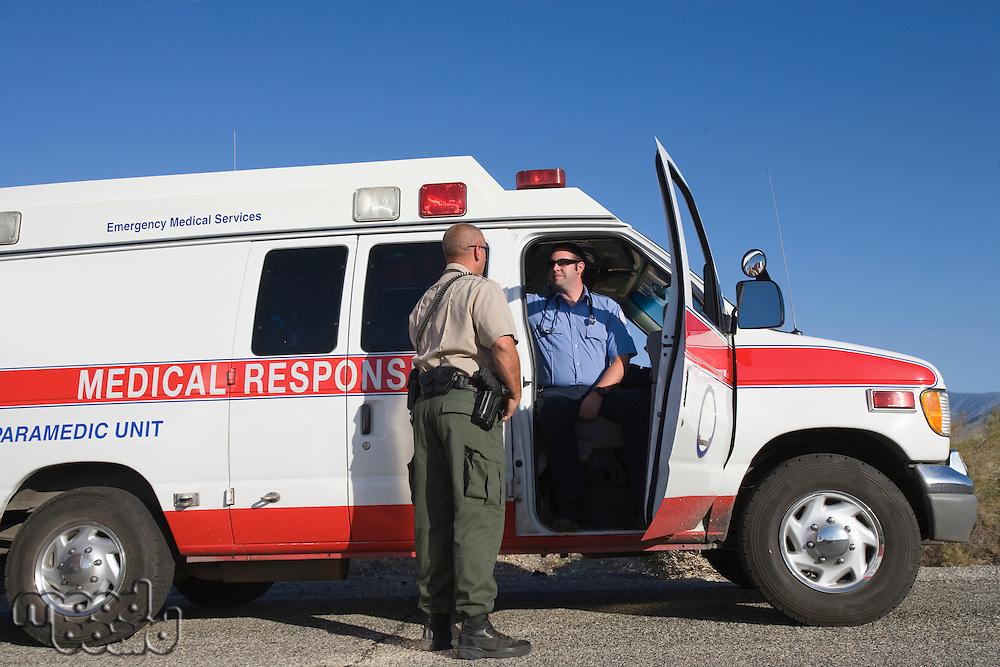 Police man talking with paramedic