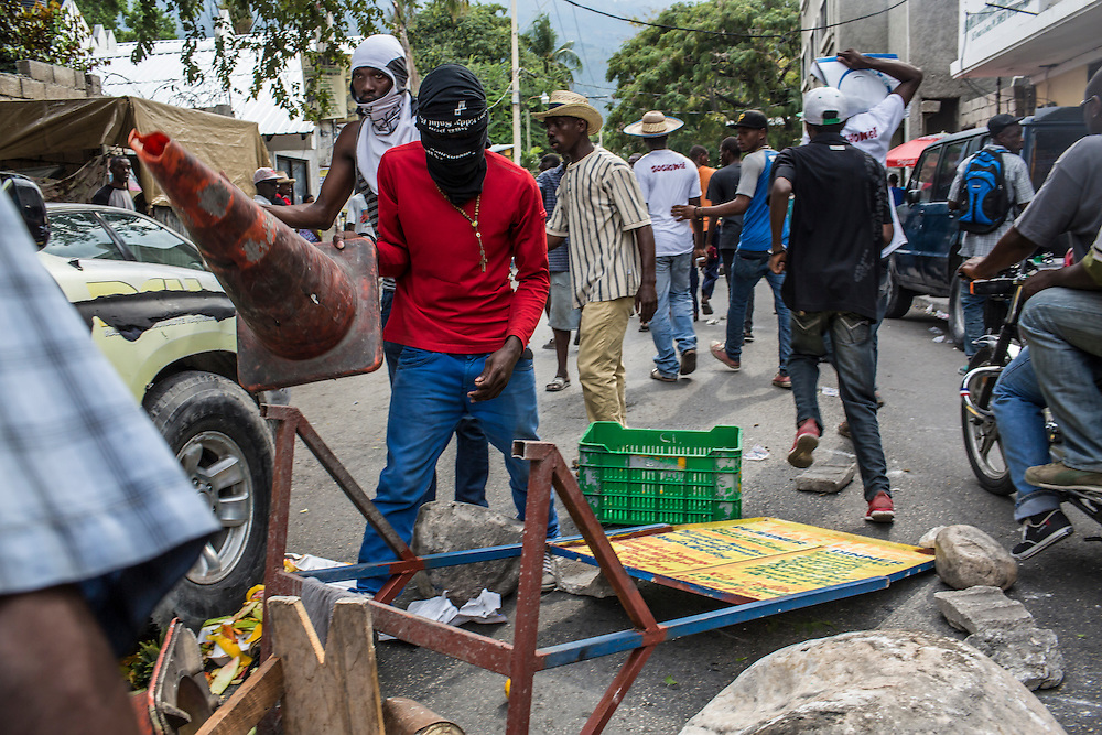 Anti-government demonstraters build barriers in the road during a protest on Tuesday, December 16, 2014 in Port-au-Prince, Haiti. President Michel Martelly was elected in 2010 with great hope for reforms, but in the wake of slow recovery and parliamentary elections that are three years overdue, his popularity has suffered tremendously, forcing Prime Minister Laurent Lamothe to resign.
