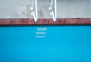 The ladder and steps of a clear, shocking aquamarine pool.