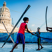 Young boys play swords on a rooftop overlooking Havana's Capital Building. For hours they ran, played and laughed.