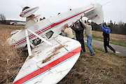 From left, Mike Mulder, Ken Littlejohn, Bob Aiken and Sgt. Ryan King of the Blaine Police department try to push over a single engine Piper Tri-Pacer air plane Friday, Dec 22, 2006, after Littlejohn crashed it into a field after taking off from the Blaine Municipal Airport that afternoon. Sgt. King said that Littlejohn was on his third circuit of touch and gos when he experienced an engine failure at an altitude of approximately 300 feet where he then preformed an emergency landing. The plane landed up right and then flipped over. Littlejohn was flying alone and  experienced several minor cuts.