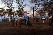 A cowgirl rides her competition horse towards the arena in Barretos, Brazil, Wednesday, Aug. 22, 2012. Brazil is on a quick path to become a global power. Rising economy, big infrastructure projects, an emerging and eager consuming middle class and the booming national industry are the evidences and consequences of the wealth in the southern nation. But the often hidden source of all this wealth falls far from the luring Rio beaches or the Kolkata-New York mix that Sao Paulo is. Behind texan hats and a similar attitude the countrymen display their power through a myriad of projects, festivals and behavior visually analyzed here.