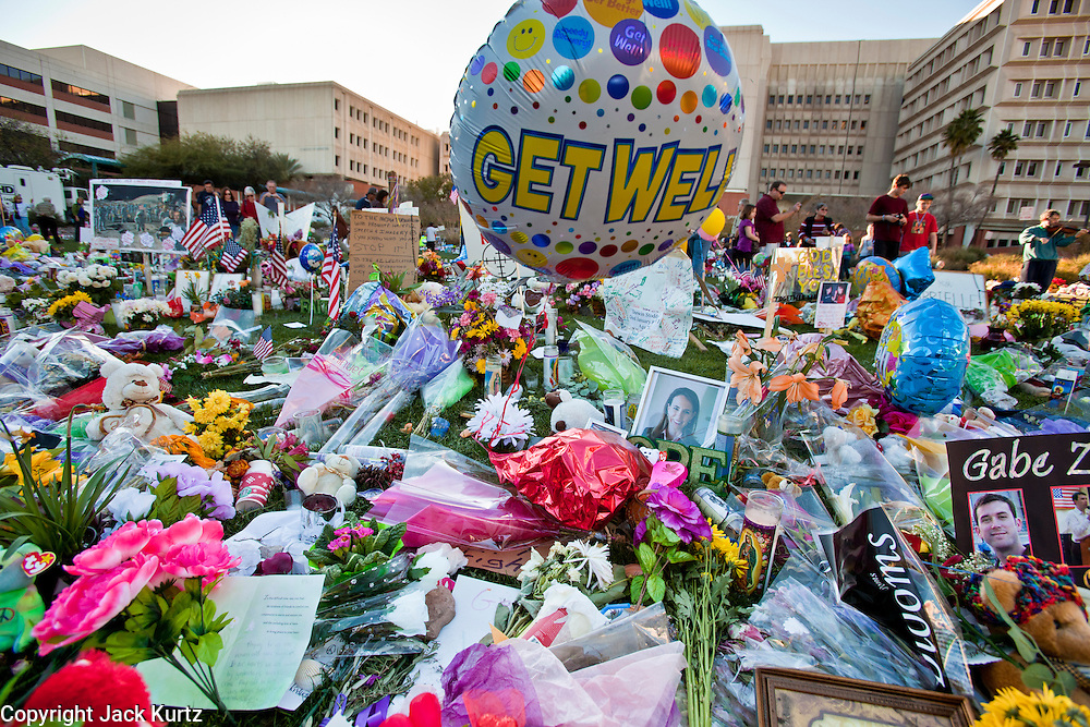 "15 JANUARY 2011 - TUCSON, AZ: The memorial on the lawn in front of the University Medical Center in Tucson, AZ, Saturday, January 15. The memorial has been growing since the mass shooting last week. Six people were killed and 14 injured in the shooting spree at a ""Congress on Your Corner"" event hosted by Congresswoman Gabrielle Giffords at a Safeway grocery store in north Tucson on January 8. Congresswoman Giffords, the intended target of the attack, was shot in the head and seriously injured in the attack. She is hospitalized at UMC. The alleged gunman, Jared Lee Loughner, was wrestled to the ground by bystanders when he stopped shooting to reload the Glock 19 semi-automatic pistol. Loughner is currently in federal custody at a medium security prison near Phoenix.  Photo by Jack Kurtz"