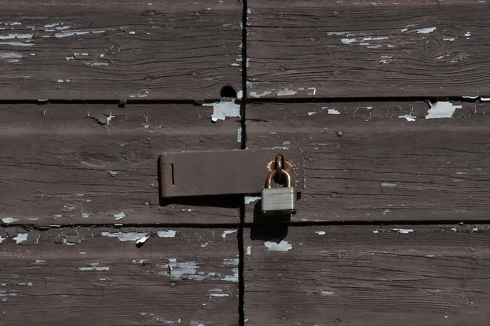 An old locked padlock secures a old wooden door