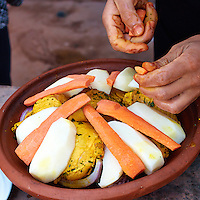 Adding Carrots to Marinated Chicken in the Tagine -- Cooking School and Meal in the Atlas Mountains of Morocco. Image taken with a Nikon 1 V2 camera and 18.5 mm f/1.8 lens (ISO 200, 18.5 mm, f/2.8, 1/500 sec). Semester at Sea Spring 2013 Enrichment Voyage Field Trip.