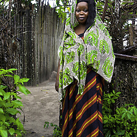 Maima, a Liberian Refugee, stands in front of her makeshift home at Krisan Refugee Camp in Ghana