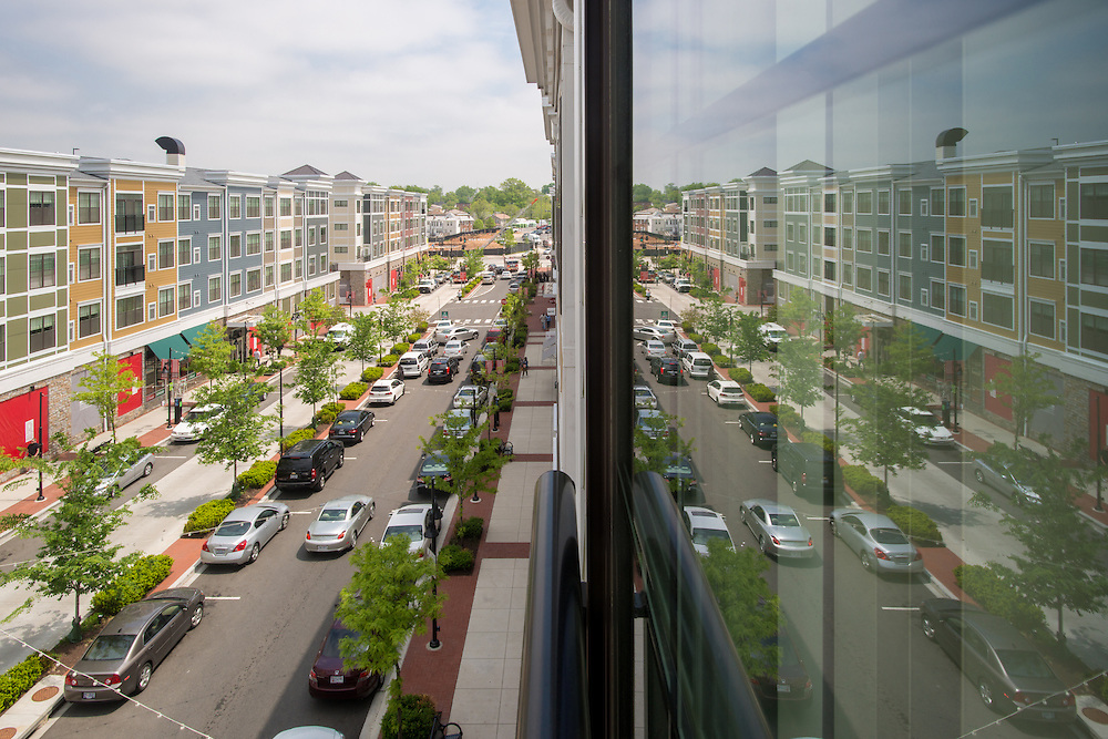 Window reflections showing shopping, town homes, and cars at Rhode Island Row in<br /> Washington DC, USA